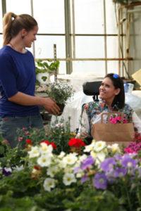 Bilde av en kvinne i rullestol som kjøper blomster. En annen kvinner holder fram en blomst. Fargerike blomster i forgrunnen.