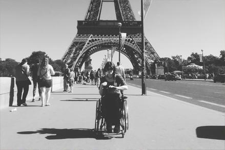 Bilde av rullestolbruker Ingrid Thunem foran Eiffeltårnet i Paris.