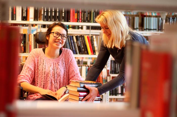 Bilde av en kvinne i rullestol på et bibliotek. En annen kvinne plasserer bøker på bordet foran henne.