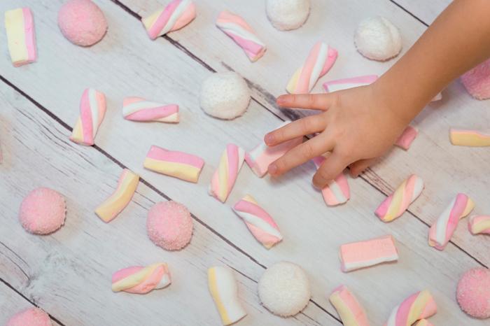 Bilde av armen til et barn som er i ferd med å plukke opp godteri fra et gulv.