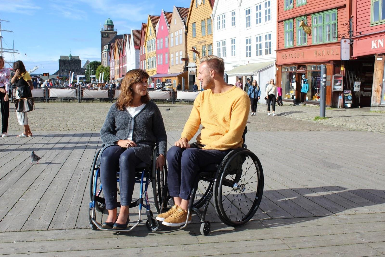 Bilde fra Brygga i Bergen. I fokus er Bergens varaordfører og nestleder i helse og sosialkomiteen, Marita Moltu, som prøver ut rullestol. Hun sitter ved siden av BPA-konsulent Lars Ivar Eilerås.