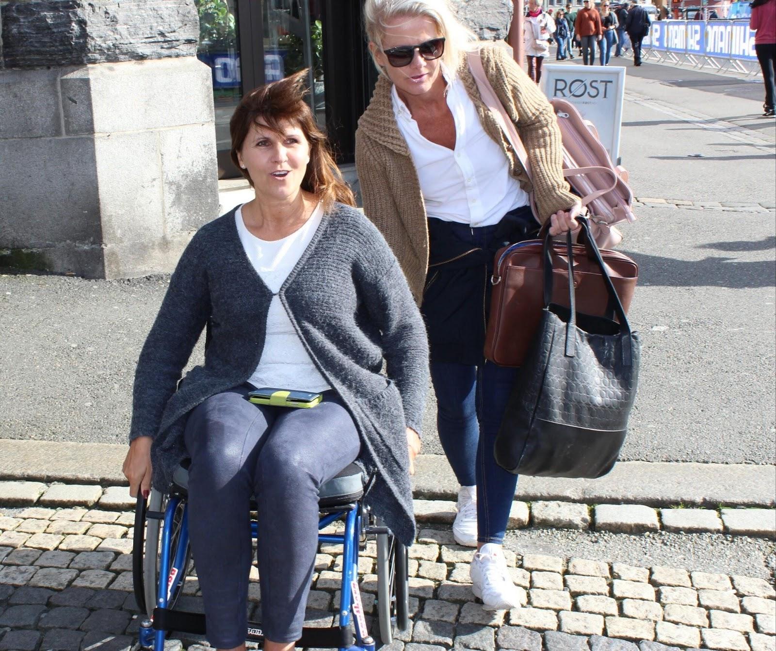 Bilde av Bergens varaordfører Marita Moltu sittende i rullestol sammen med en assistent fra Prima Assistanse.