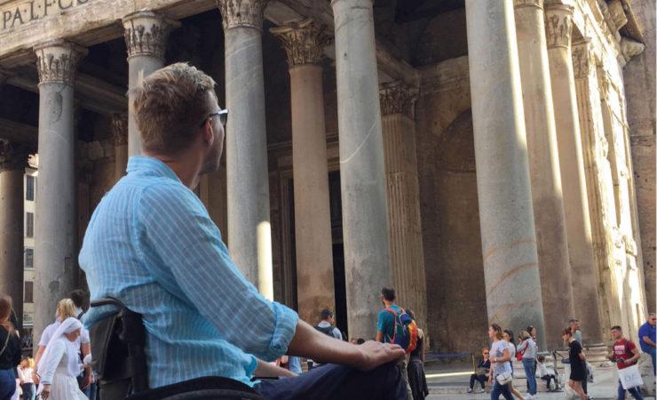 Bilde av BPA-konsulent Lars Ivar Eilerås i rullestol iført en blå-stripete skjorte. Han kikker opp mot det historiske bygget Pantheon i Roma.
