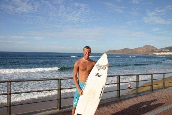 Bilde av artikkelforfatter ved en strand. Han står og holder et surfebrett mens han smiler mot kameraet. I bakgrunnen skimtes et gelender, en strand, bølger og en fjellformasjon.