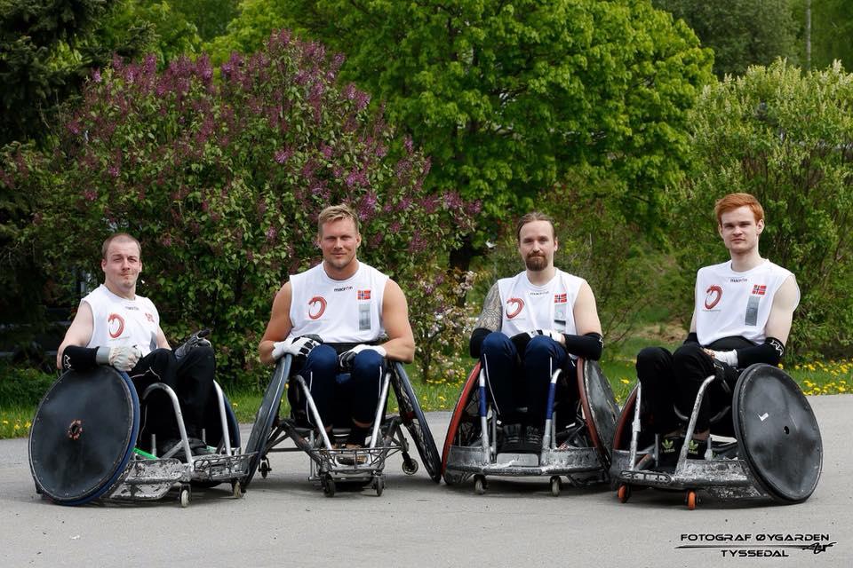 Bilde av Lars Ivar Eilerås sammen med tre lagkamerater i rullestolrugby. De sitter alle i rullestol ved siden av hverandre i hvite trøyer. I bakgrunnen skimtes trær.