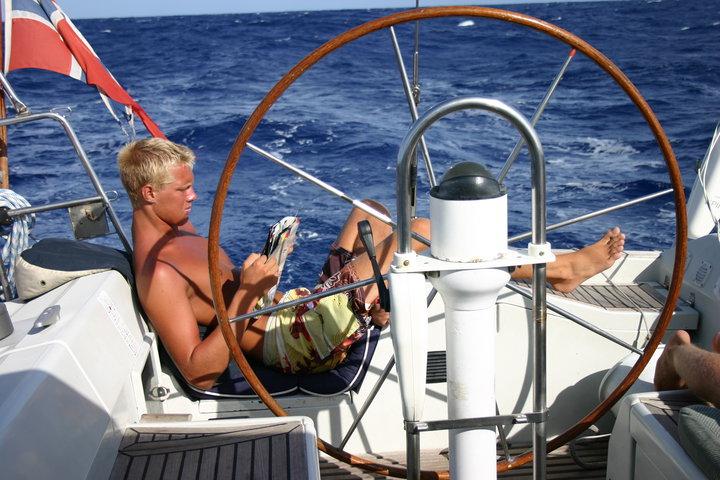 Bilde av artikkelskribent som sitter lettere henslengt akterut i en seilbåt. Han leser i et blad mens han ser ut til å sole seg. I bakgrunnen er det kun hav og i forgrunnen er seilbåtens ror.