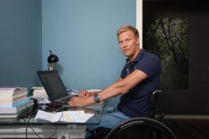 Bilde av artikkelskribent som sitter og jobber foran en laptop i rullestol. Han lener armene mot skrivebordet mens han kikker mot kameraet.