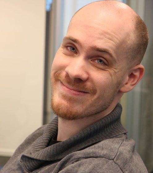 Portrettbilde av en smilende Kristoffer Svendsen som ser inn i kamera. I bakgrunnen kan en vegg og en dør fra arbeidsplassen hans skimtes.