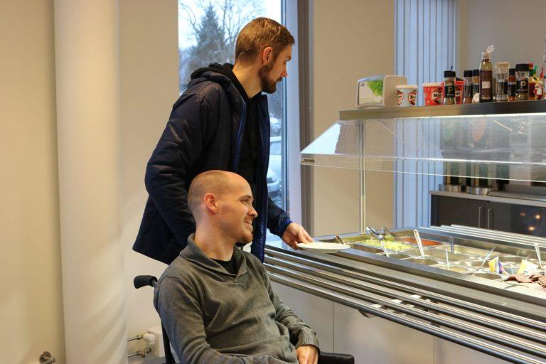 Bilde som viser Kristoffer Svendsen og hans funksjonsassistent, Abraham Heggvik, i kantinen på Kristoffers arbeidsplass. Kristoffer sitter i rullestol ved siden av salatbaren og kikker bort på utvalget. Hans funksjonsassistent står bak ham og holder en tallerken i hånden.