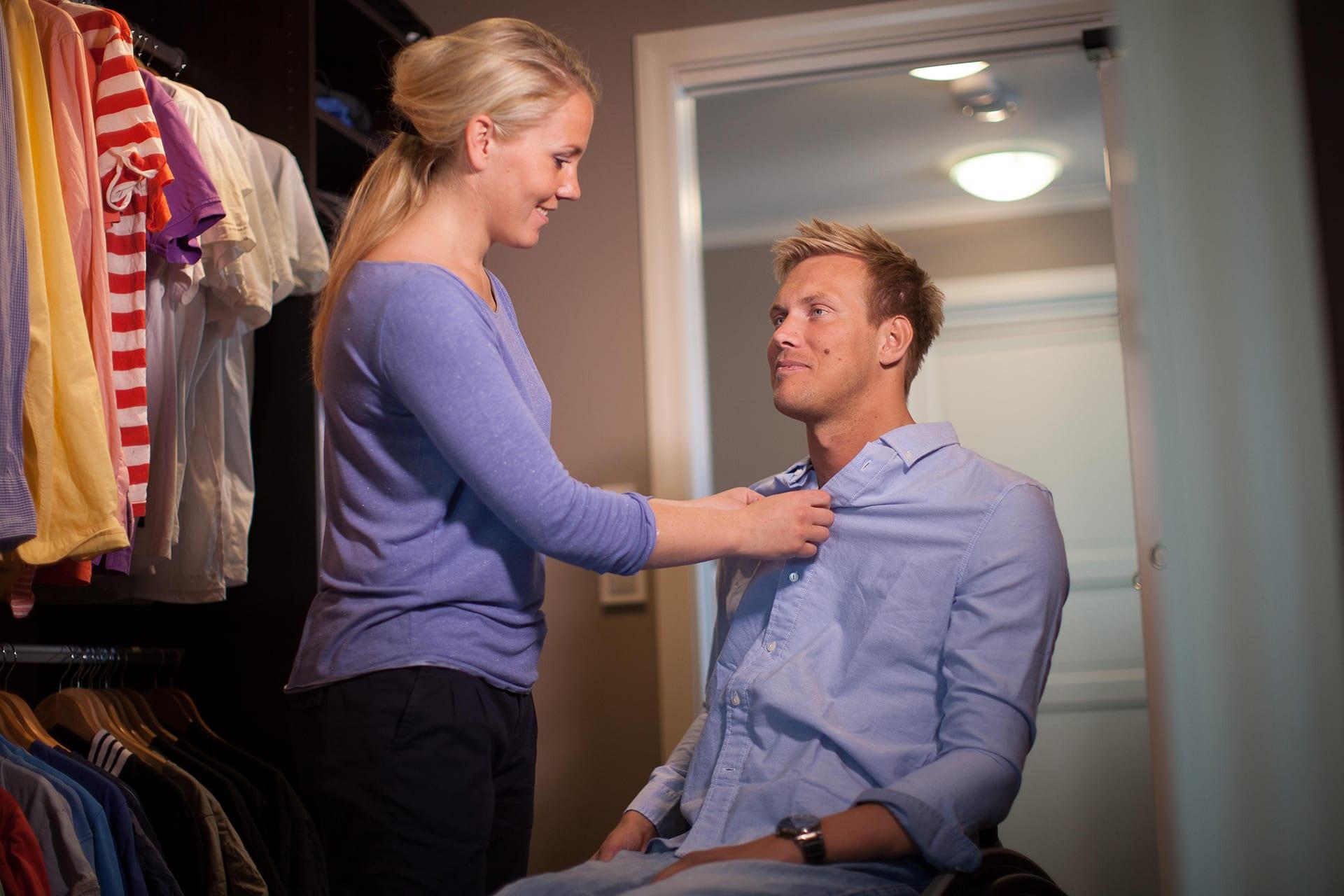 Bilde av artikkelskribent og hans kvinnelige assistent. Han sitter i rullestol mens han kikker mot assistenten. Assistenten hjelper ham med å kneppe igjen en blå skjorte. De befinner seg i et rom med en rekke t-skjorter og skjorter på venstre side.