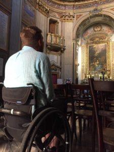 Bilde av artikkelskribent i rullestol inne i en kirke. Han sitter med ryggen til kameraet og kikker mot alteret. Han er alene.