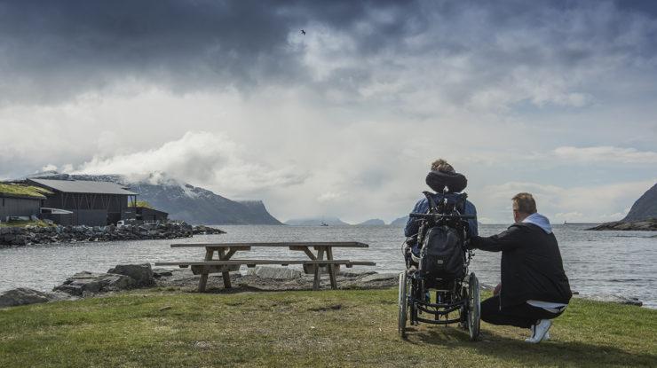 Bilde av en kvinne i rullestol med en mann som sitter på kne ved siden av henne. De har begge ryggen mot kameraet mens de kikker ut mot en fjord. Foran dem er et rasteplassbord.