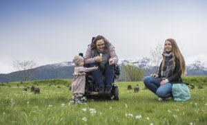 Bilde av artikkelskribent, hennes datter og assistent. Artikkelskribenten sitter i rullestol og peker mot såpebobler. Hennes datter står ved siden av henne og rekker ut hånden. Assistenten sitter ved siden av dem og observerer. De befinner seg på en gresslette med fjell i bakgrunnen.
