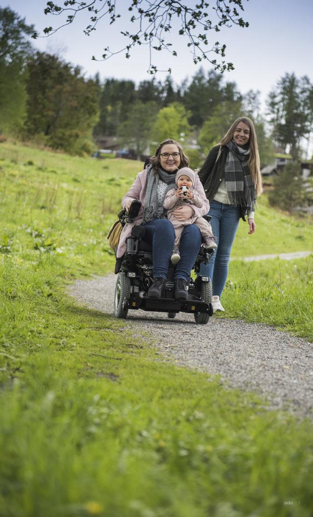 Bilde av en smilende kvinne i rullestol. Hun kikker mot kamera med en baby på fanget. Ved siden av henne står en kvinnelig assistent og smiler mot dem. De befinner seg på en sti omringet av grønt gress.