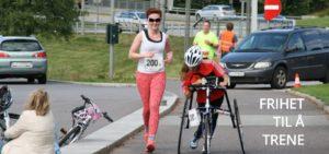 Bilde av parautøver Marte Åsvang med løpesykkel og en annen kvinne uten løpesykkel. De deltar i et RaceRunning-løp og løper begge nedover en vei. I bakgrunnen skimtes en bil og frivillige.