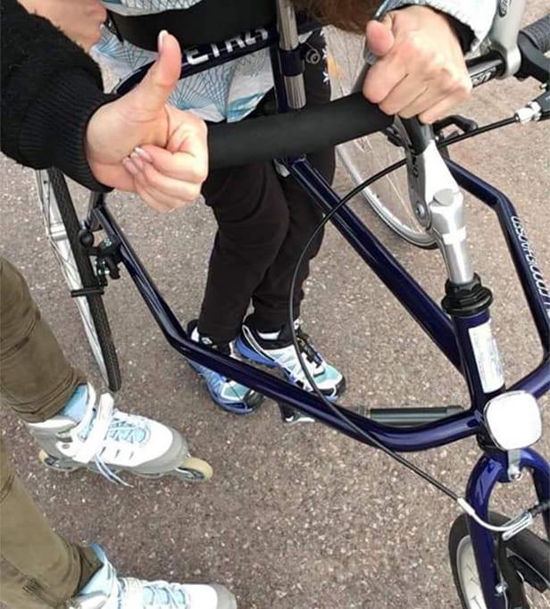Nærbilde av Marte Åsvangs bein i løpesykkelen. Hun og en annen kvinne holder tommelen opp mot kameraet.