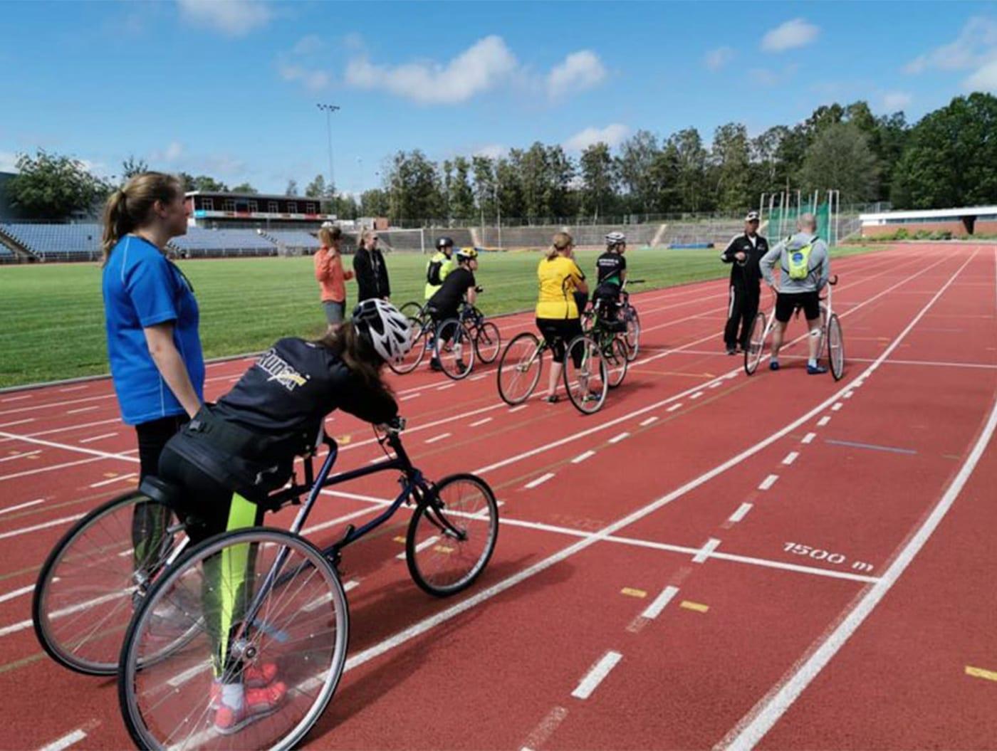 Bilde av en løpebane med fem utøvere i løpesykler. De har alle ryggen mot kameraet og ser ut til å gjøre seg klare til et løp.