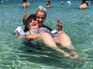 Bilde av Linnea og hennes assistent i vannet. Linnea flyter på ryggen og smiler, mens assistenten holder fast i henne. Hun smiler også. I bakgrunnen skimtes andre badende.