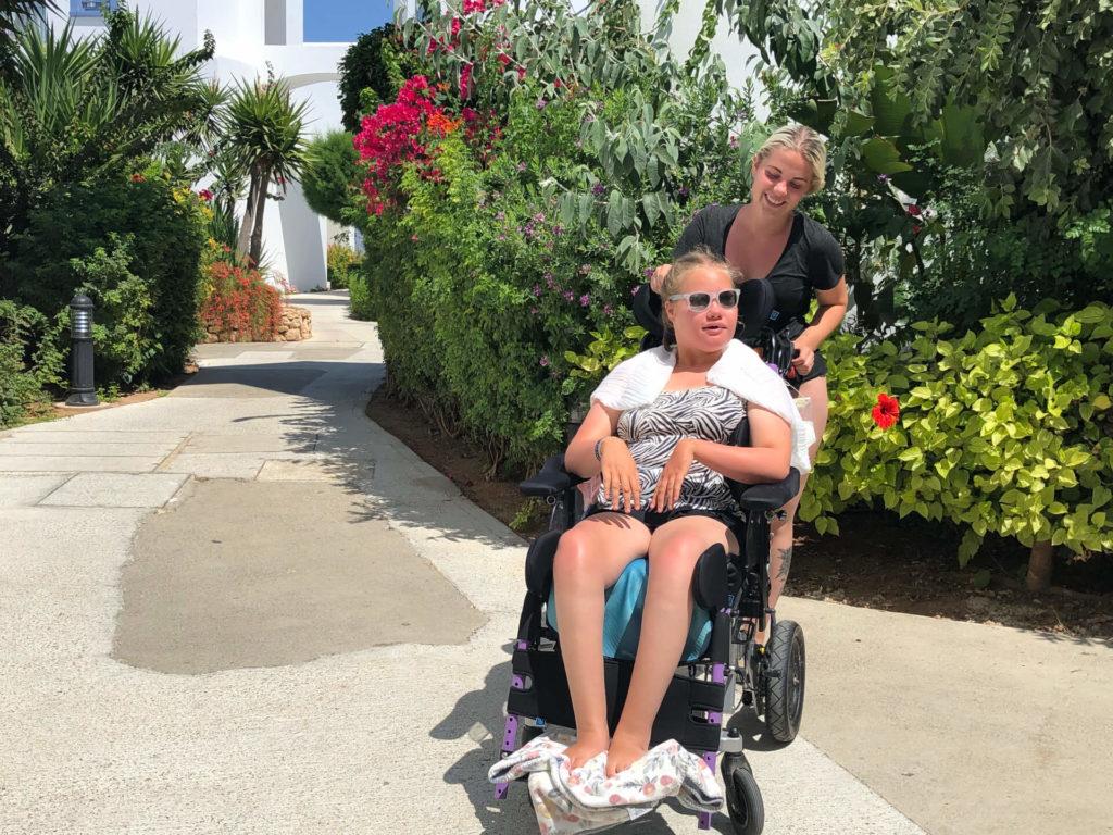 Bilde av Linnea og hennes assistent. Linnea er kledd i topp og shorts, med solbriller på. Assistenten står bak henne og holder smilende fast i rullestolen hennes. Det er en rekke trær i bakgrunnen.