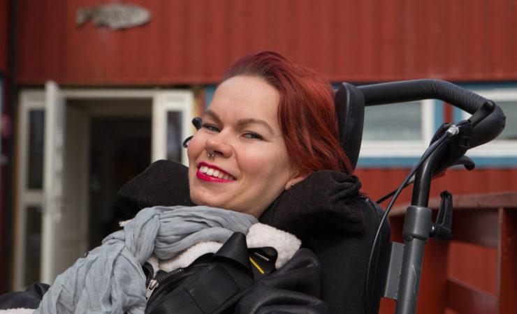 Nærbilde av Malin Pedersen. Hun kikker smilende mot kamera. Hun har ring i nesa, rødt hår og et grått skjerf. I bakgrunnen skimtes et rødt bygg med en åpen dør.