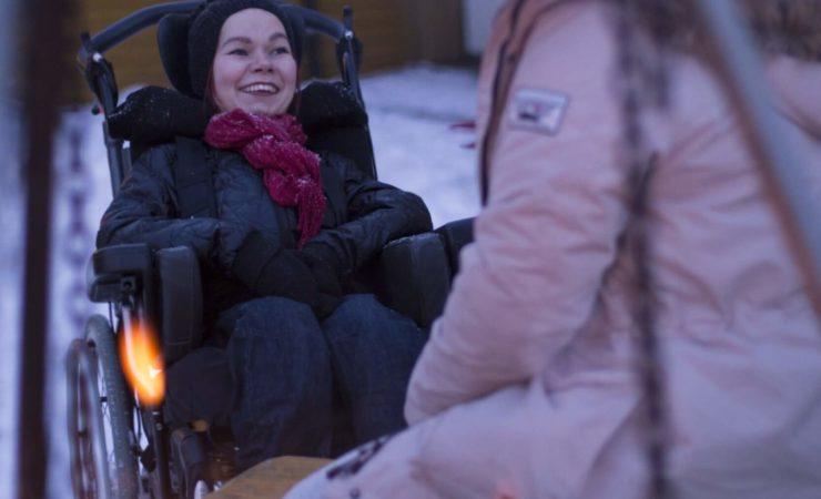 Bilde av Malin Pedersen i rullestol som kikker smilende mot en assistent. Assistenten sitter med ryggen mot kameraet og man skimter kun jakken hennes. I bakgrunnen er bakken snøbelagt.
