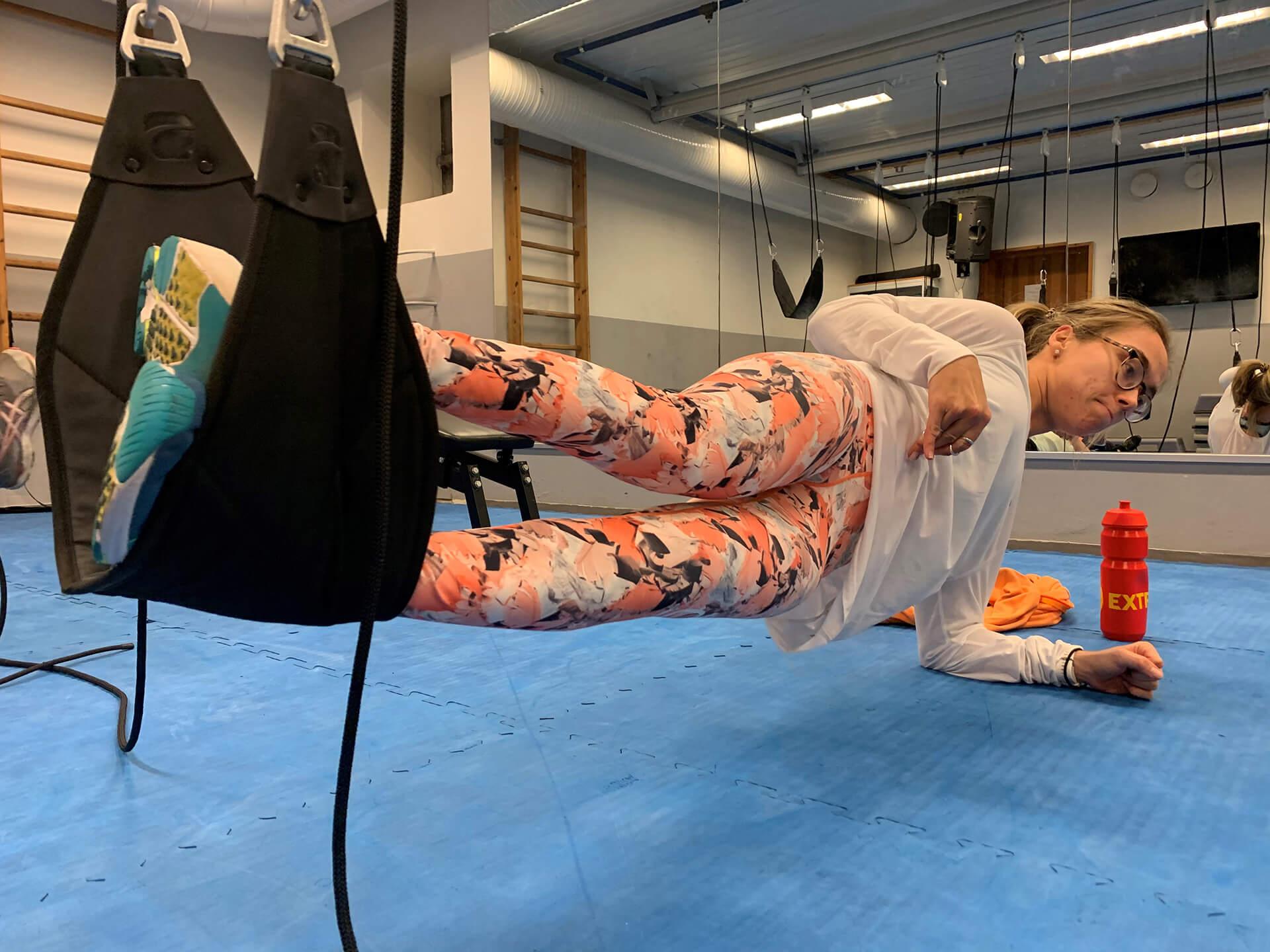 Bilde av Sofie Østerbø Jansen som trener innendørs. Hun lener seg mot armen mens føttene ligger samlet i en svart slynge som svever over bakken.