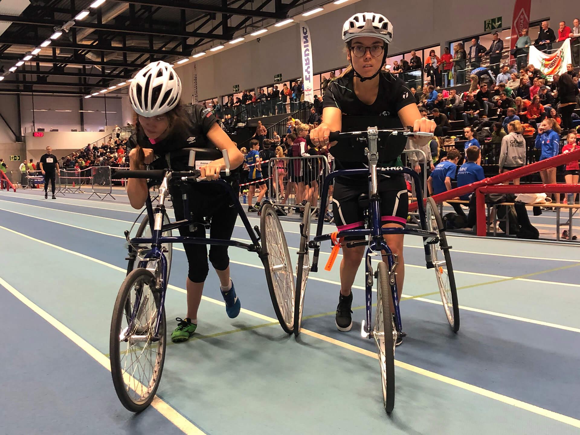 Bilde av artikkelskribent Sofie Østerbø Jansen og en annen utøver. De er begge på banen for å gjennomføre et løp i Racerunning. Sofie kikker inn i kamera mens hun holder rundt løpesykkelen.
