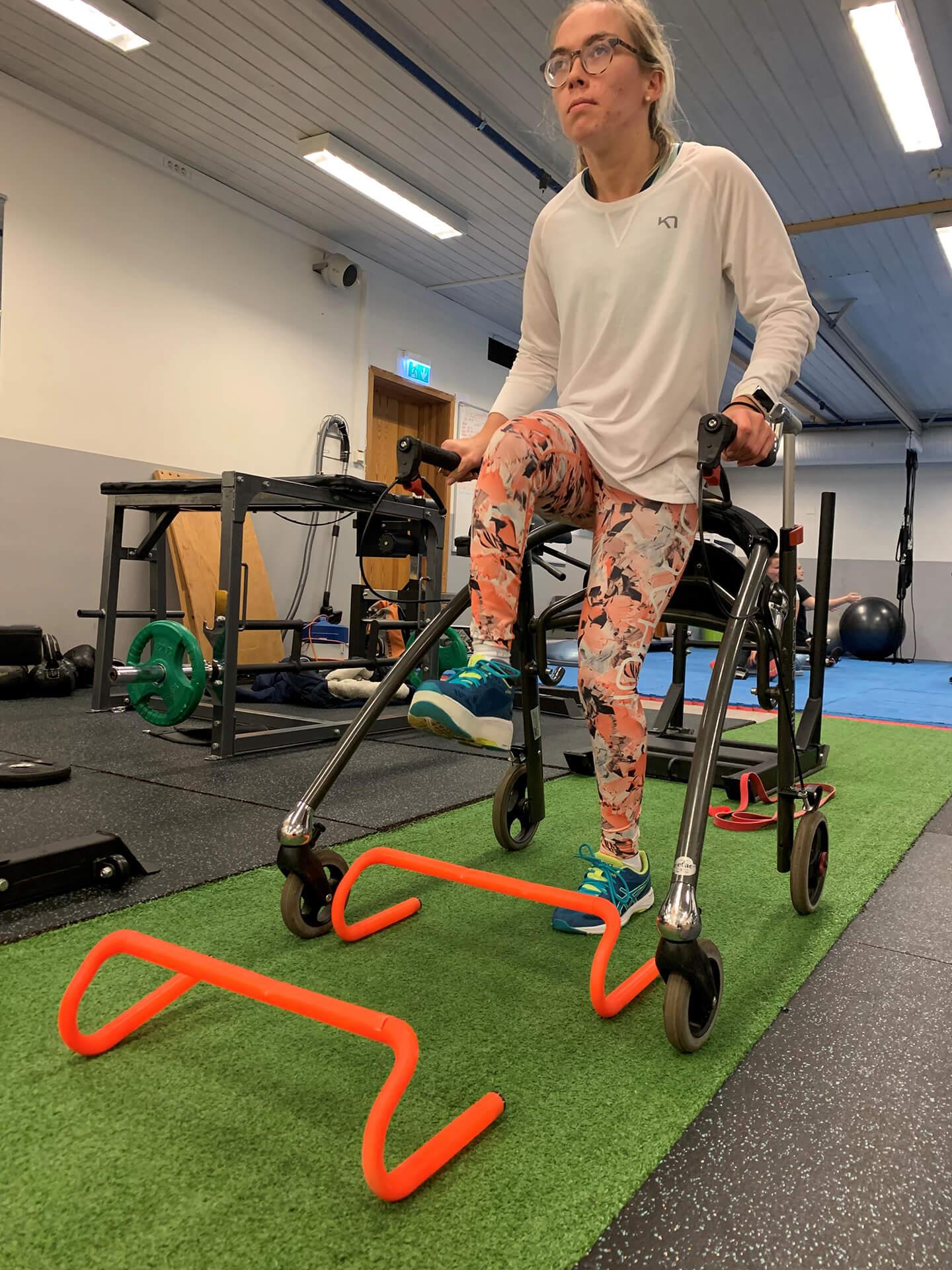 Bilde av Sofie Østerbø Jansen som trener innendørs. Hun lener seg mot et apparat med fire hjul mens hun beveger seg over hindre.