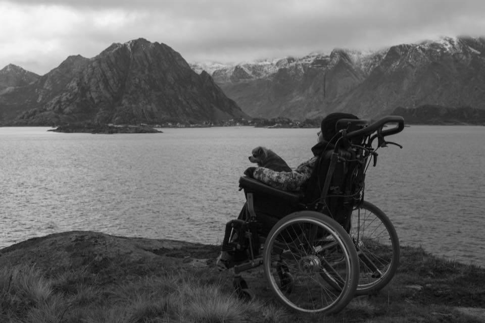 Bilde av artikkelskribent som sitter ute i rullestol med en hund på fanget. De kikker begge ut mot horisonten. I bakgrunnen skimtes vann og fjellformasjoner.