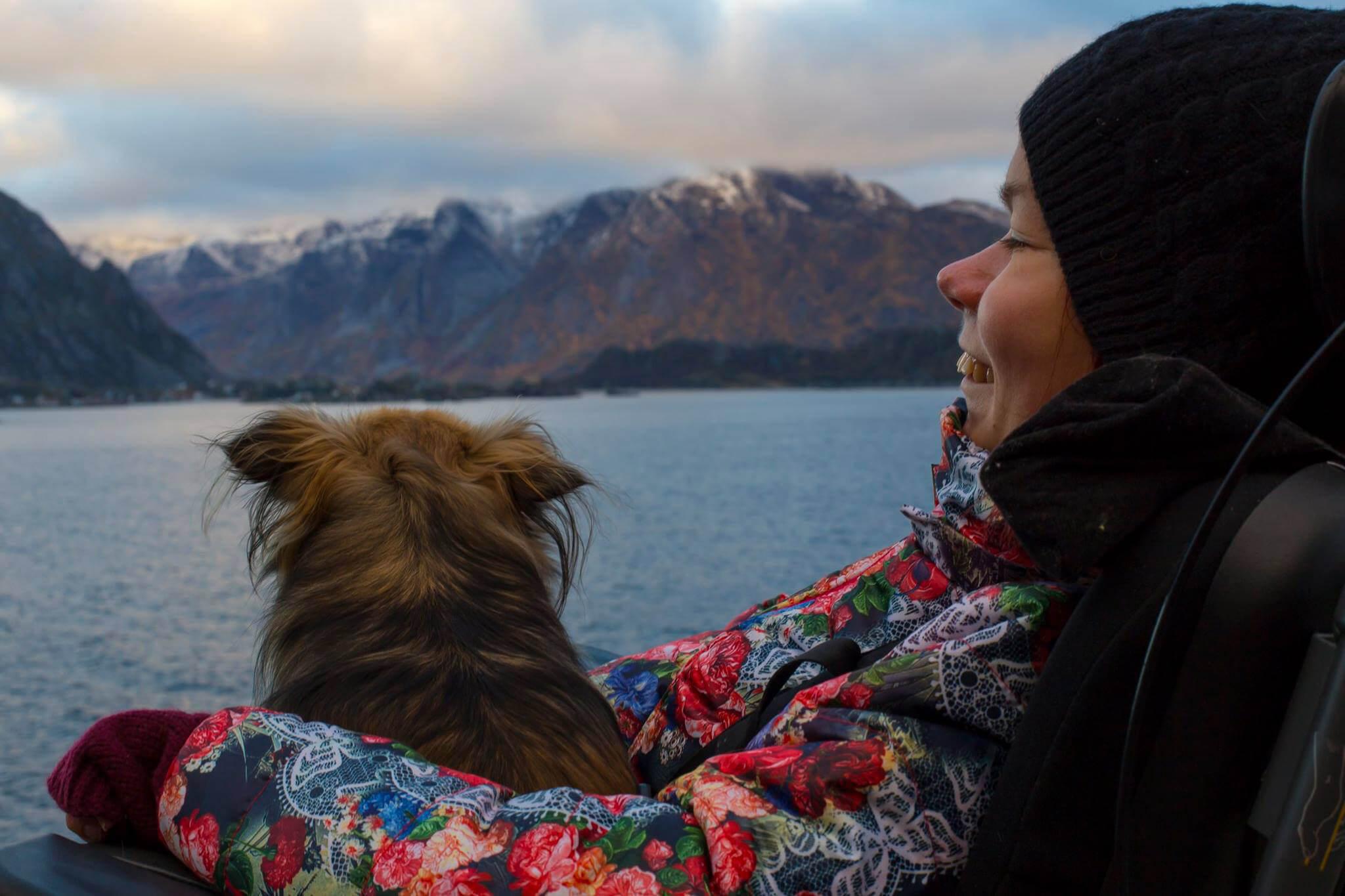 Nærbilde av artikkelskribent som sitter ute. Hun har en hund på fanget og de kikker begge ut mot fjorden. I bakgrunnen skimtes vann og fjellformasjoner.