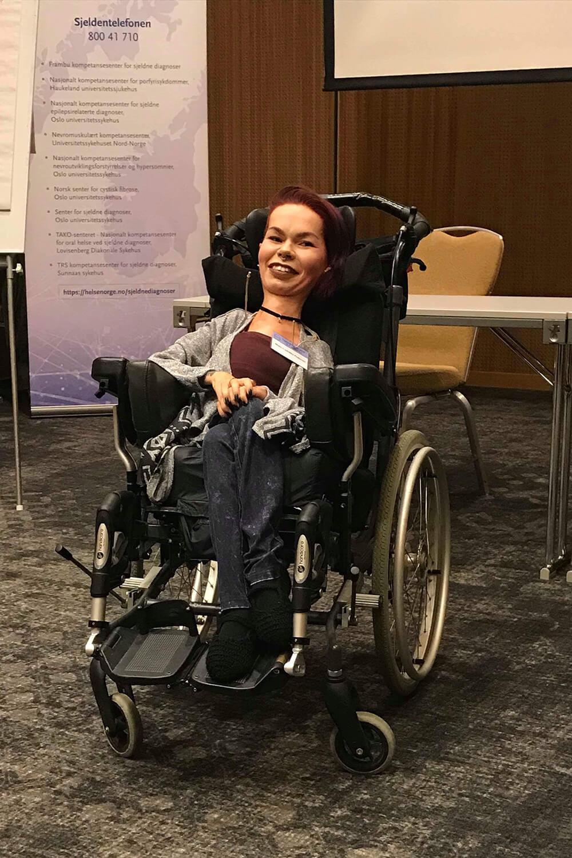 Bilde av Malin i et lokale. Hun sitter smilende i rullestol og kikker mot kameraet. I bakgrunnen skimtes et bord, en stol og en banner.