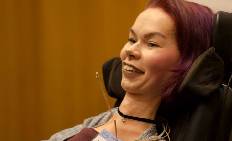 Nærbilde av Malin, blogger for Prima Assistanse. Bildet er tatt fra siden mens hun kikker mot noe utenfor bildet. Hun lener hodet mot rullestolen.