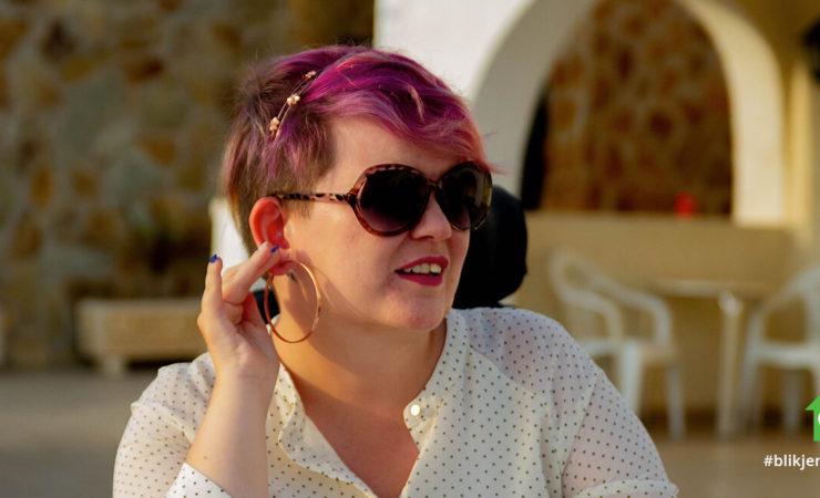 Nærbilde av Kine Lyngås. Hun kikker til siden mens hun berører en ørering med den ene hånden. Hun har på seg en prikkete skjorte og solbriller.