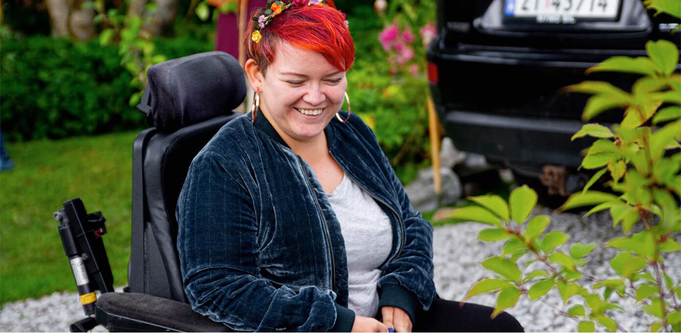 Bilde av Kine Lyngås som kikker ned mot bakken. Hun har blomster i håret og sitter i rullestol i en hage. I bakgrunnen skimtes gress og en bil.