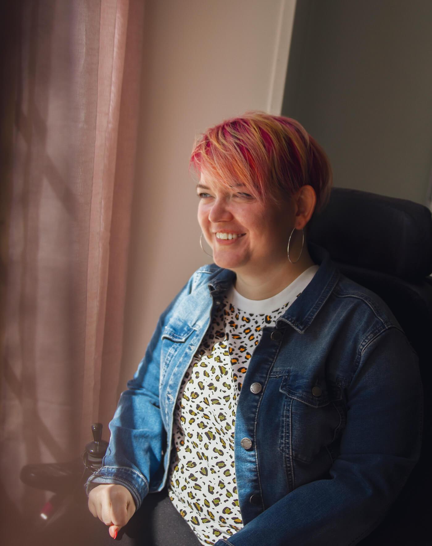 Bilde av Kine Lyngås som kikker til siden. Hun sitter smilende i rullestol. I bakgrunnen skimtes gardiner og en hvit vegg.