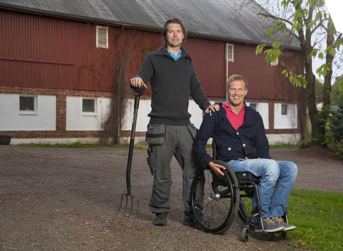 Bilde av Lars Ivar Eilerås, markedskoordinator i Prima Assistanse. Han sitter i rullestol og kikker smilende mot kameraet. Ved siden av seg står hans bror med en høygaffel i hånden. I bakgrunnen skimtes et gårdsbygg.