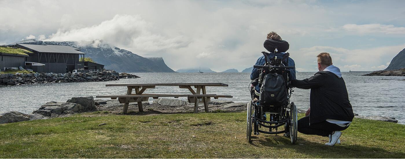 Bilde av en kvinne i rullestol med en mann som sitter på kne ved siden av henne. De har begge ryggen mot kameraet og kikker ut mot en fjord. Foran dem er et rasteplassbord.