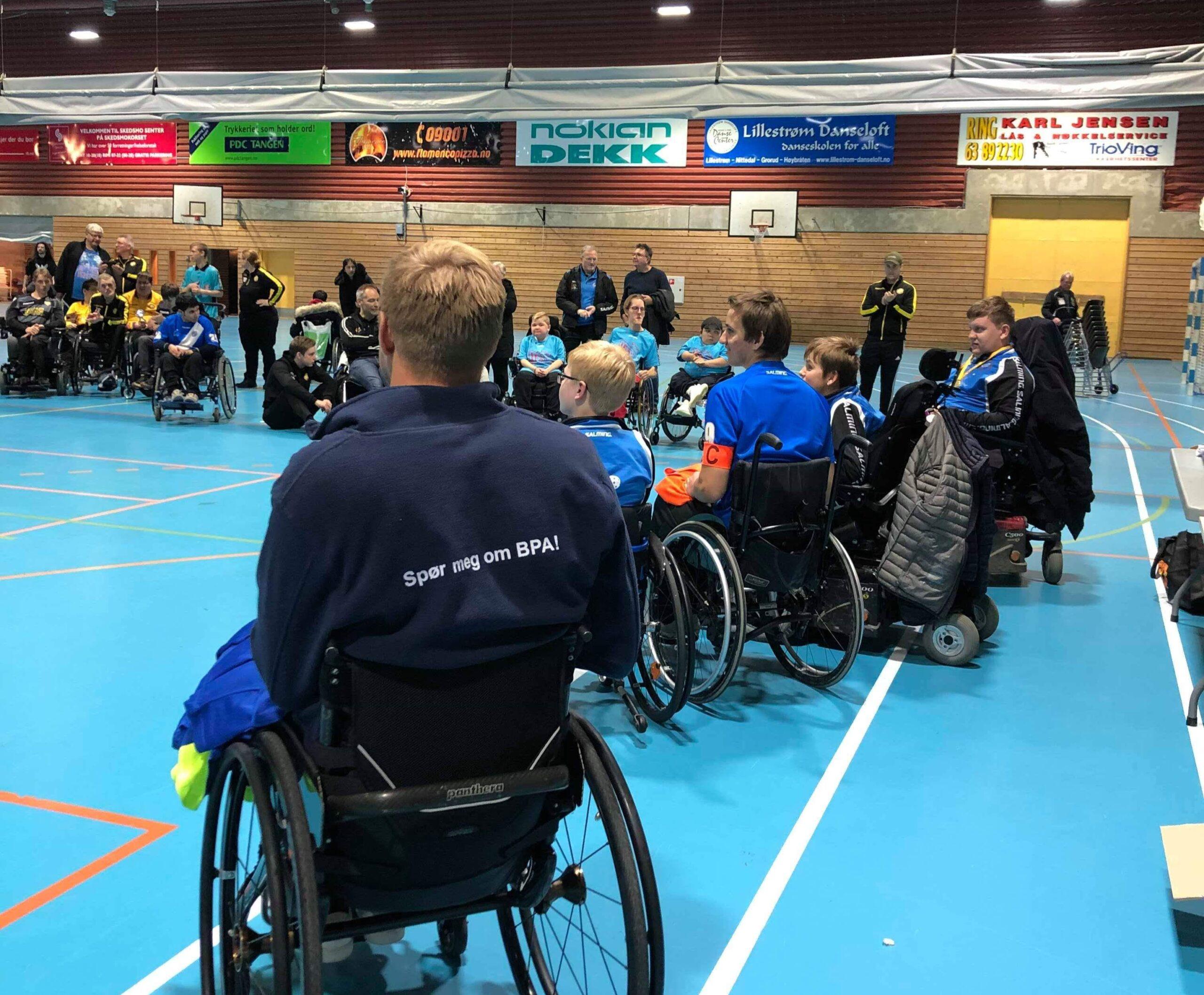 Bilde fra en innendørs treningsøkt i rullestolrugby. Lars Ivar Eilerås har ryggen mot kamera. Han har på seg en genser med påskriften «spør meg om BPA». Det er en rekke unge spillere i rullestol som kikker ut mot banen.