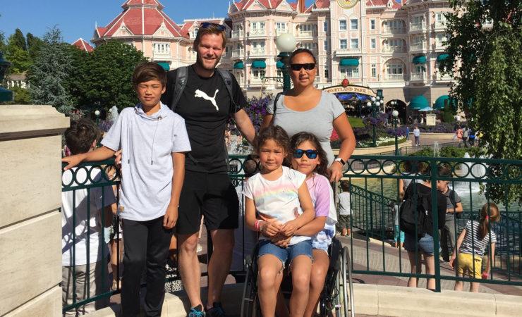 Bilde av BPA-koordinator Elisabeth Lillegrend sammen med sin ektemann, sønn og to døtre. Den ene datteren sitter i rullestol med sin søster på fanget. De andre står bak dem. I bakgrunnen skimtes et bygg med påskriften Disneyland.