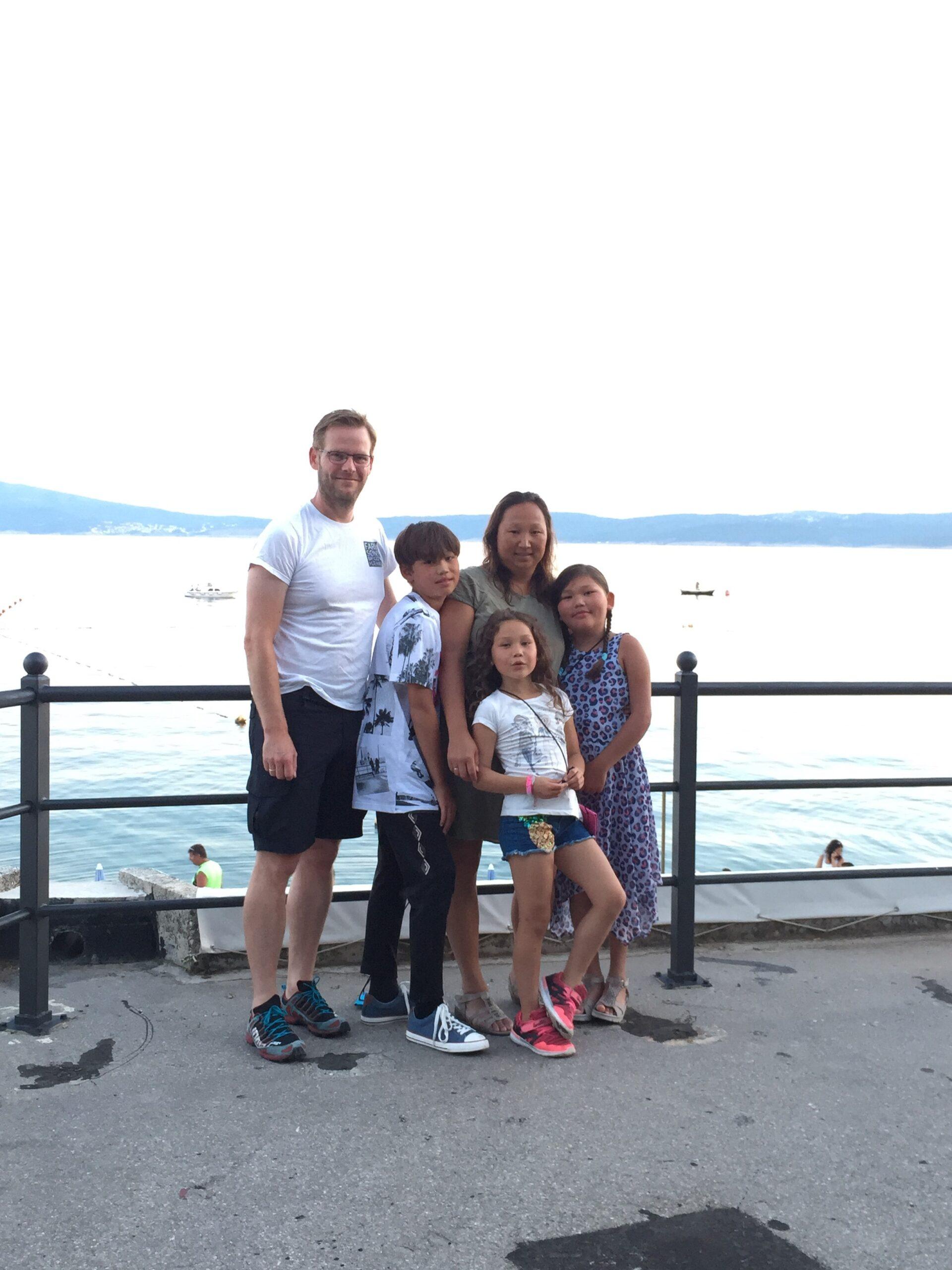 Bilde av BPA-koordinator Elisabeth Lillegrend sammen med sin ektemann, sønn og to døtre. De står alle samlet foran et gelender. I bakgrunnen skimtes hav og fjellformasjoner.