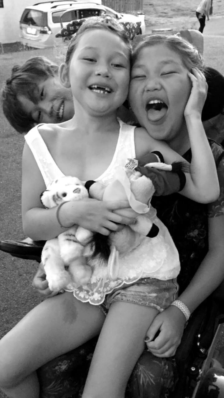 Et svart-hvitt bilde av de to døtrene og sønnen til Elisabeth Lillegrend. De gjør seg til for kameraet ved å lage grimaser.
