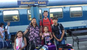 Bilde av BPA-koordinator Elisabeth Lillegrend sammen med sin ektemann, sønn og to døtre. De står samlet på en perrong med bagasje foran seg. I bakgrunnen skimtes et tog og et skilt med påskriften «Budapest – Keleti».