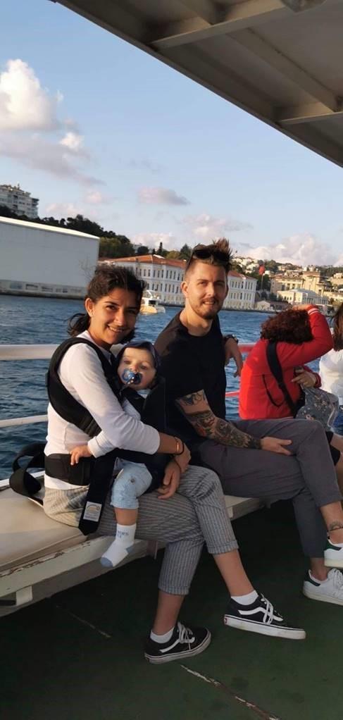 Bilde av Noor, ektemannen og datteren. De sitter sammen med andre mennesker i en båt. I bakgrunnen skimtes bygninger og vannmasse.