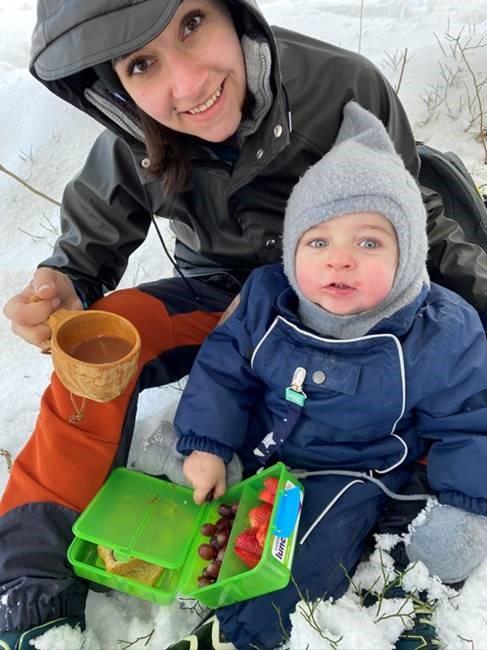 Selfie av Noor og datteren. De sitter ute i snøen. Noor holder en kopp med kakao i den ene hånden og datteren har en matboks med frukt og brødskive i fanget. De kikker begge inn i kameraet