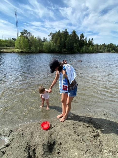 Bilde av artikkelskribent Noor på en badestrand med datteren. Noor står på en fjellformasjon i vannkanten mens hun holder hånden til datteren som står med føttene i vannet.